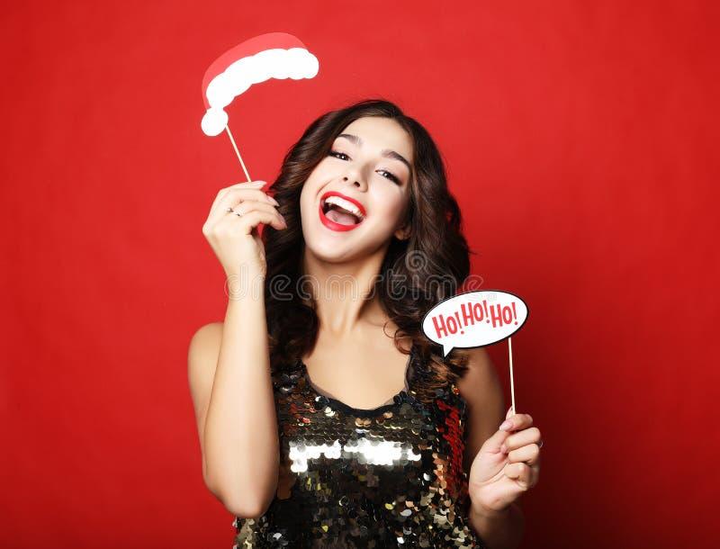 Levensstijl, vakantie en mensenconcept - de vrolijke jonge vrouw in kleding houdt steunen voor een partij en glimlacht stock foto