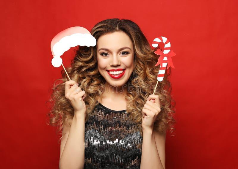 Levensstijl, vakantie en mensenconcept - de vrolijke jonge vrouw in kleding houdt steunen voor een partij en glimlacht stock afbeeldingen