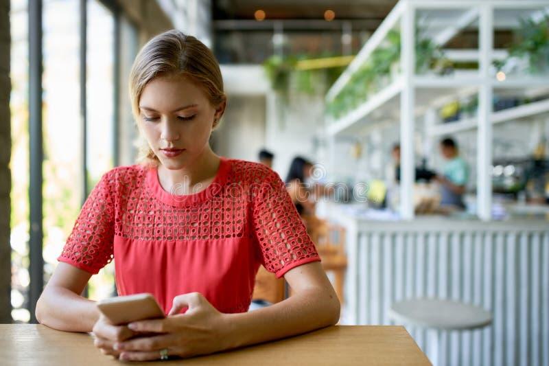 Levensstijl van het jonge blonde Kaukasische natuurlijke millennial vrouw typen op cellphone die bij moderne tropisch wordt gesch stock afbeelding