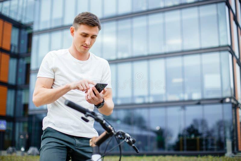 Levensstijl, vervoer, mededeling en mensenconcept - jonge mens met fiets en smartphone op stadsstraat stock afbeeldingen