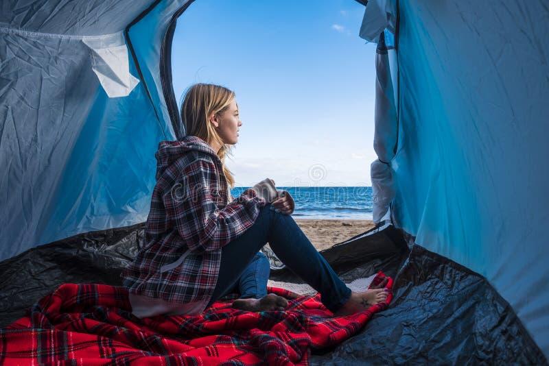 Levensstijl voor blonde beaitufl vrouw buiten haar tent dichtbij de oceaan stock foto
