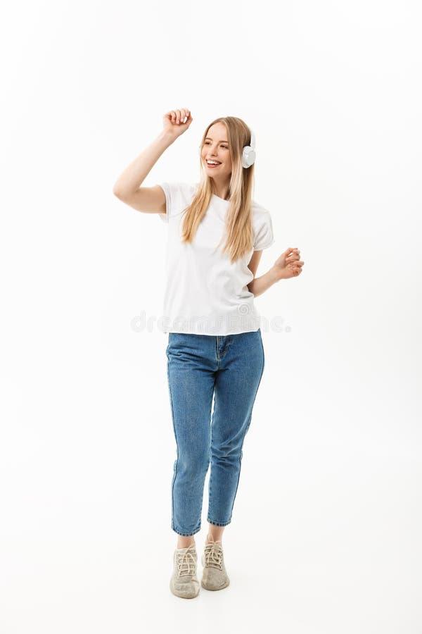 Levensstijlconcept: Portret van een vrolijke gelukkige studente die aan muziek met hoofdtelefoons luisteren terwijl geïsoleerd da stock foto