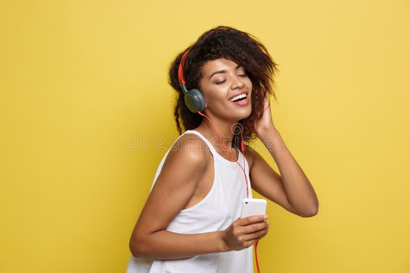 Levensstijlconcept - Portret van het mooie Afrikaanse Amerikaanse vrouw blije luisteren aan muziek op mobiele telefoon geel stock foto