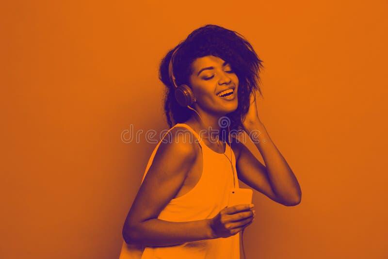 Levensstijlconcept - Portret van het mooie Afrikaanse Amerikaanse vrouw blije luisteren aan muziek op mobiele telefoon geel stock afbeelding