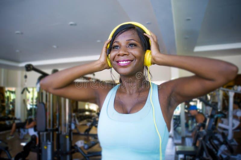Levensstijlportret bij gymnastiek van jonge gelukkige en aantrekkelijke afro Amerikaanse vrouw opleiding vrolijk bij geschiktheid royalty-vrije stock afbeelding