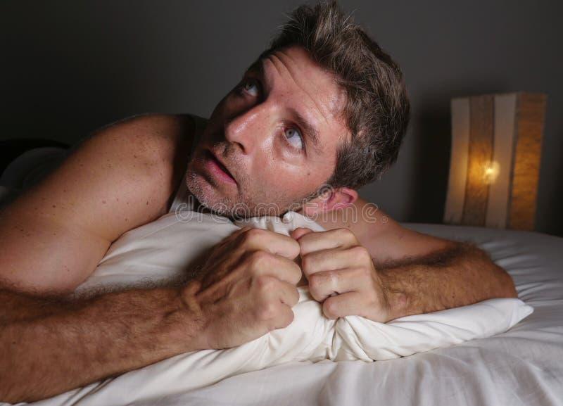 Levensstijlportret die van de jonge aantrekkelijke doen schrikken en parano?de mens in bed liggen die slechte dromen en nachtmerr royalty-vrije stock foto's