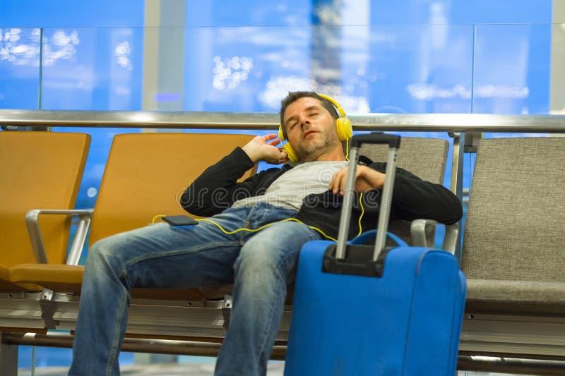 Levensstijlportret in luchthaven van de jonge aantrekkelijke en vermoeide toeristenmens die met koffer aan muziek met hoofdtelefo stock fotografie