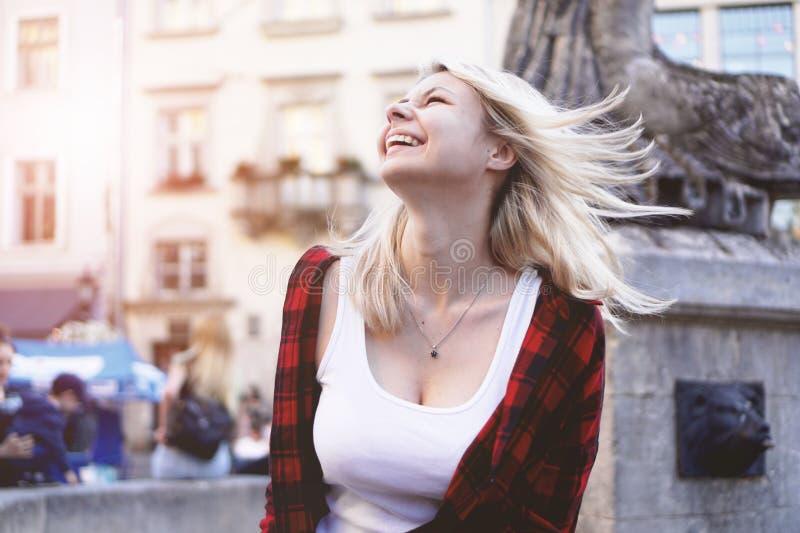 Levensstijlportret van blondemeisje die een rots rood overhemd, witte t-shirt dragen stock afbeelding