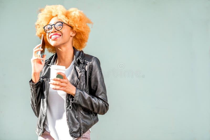 Levensstijlportret van een Afrikaanse vrouw op de groene achtergrond stock fotografie