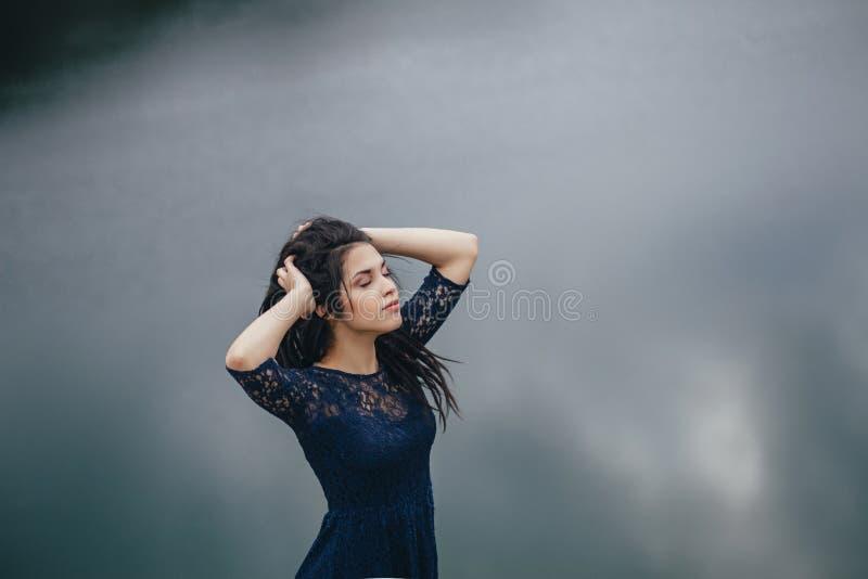 Levensstijlportret van een vrouwenbrunette op de achtergrond van het meer in het zand op een bewolkte dag Romantisch, zacht, myst royalty-vrije stock foto