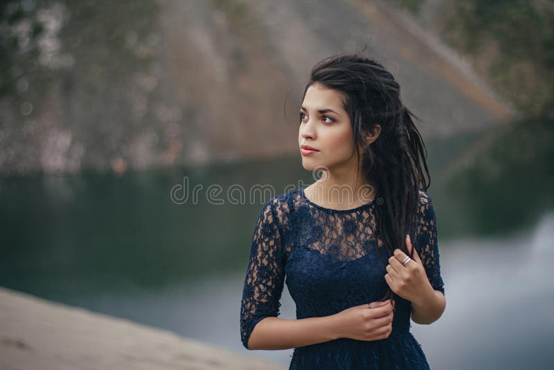 Levensstijlportret van een vrouwenbrunette op de achtergrond van het meer in het zand op een bewolkte dag Romantisch, zacht, myst stock fotografie