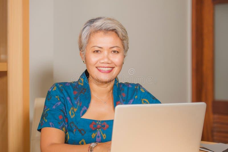 Levensstijlportret van het Gelukkige en aantrekkelijke elegante midden oude Aziatische bedrijfsvrouw werken die bij het bureau va royalty-vrije stock fotografie