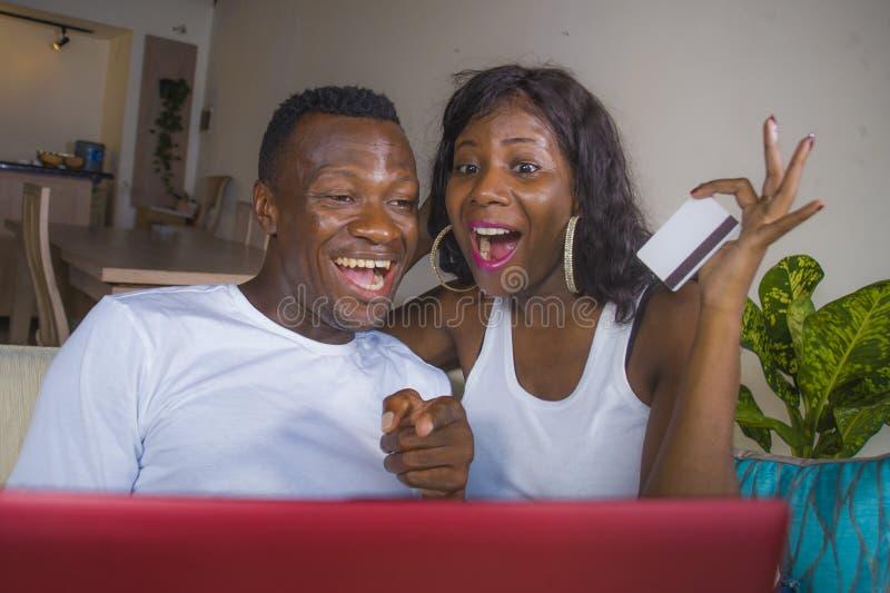 Levensstijlportret van jong gelukkig en aantrekkelijk zwart afro Amerikaans paar die genieten van gebruikend creditcard en laptop stock fotografie