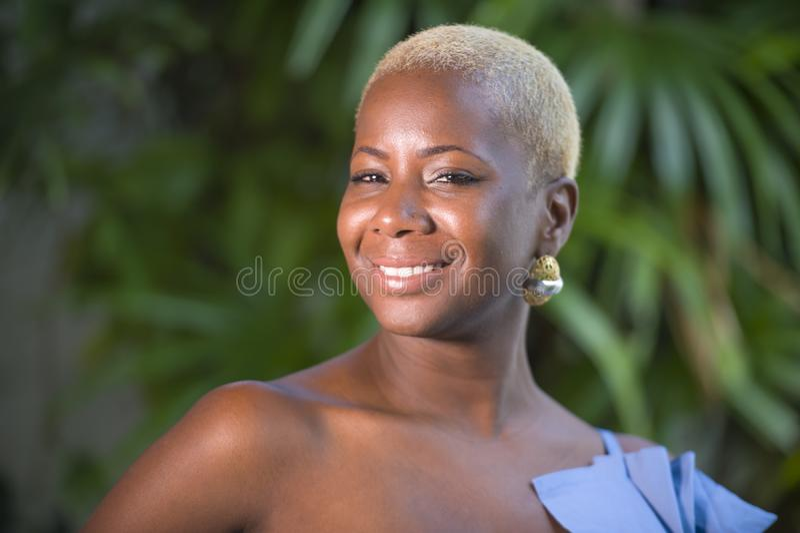 Levensstijlportret van jonge aantrekkelijke en blije zwarte Afrikaanse Amerikaanse vrouw die gelukkig stellend vrolijk thuis terr stock foto