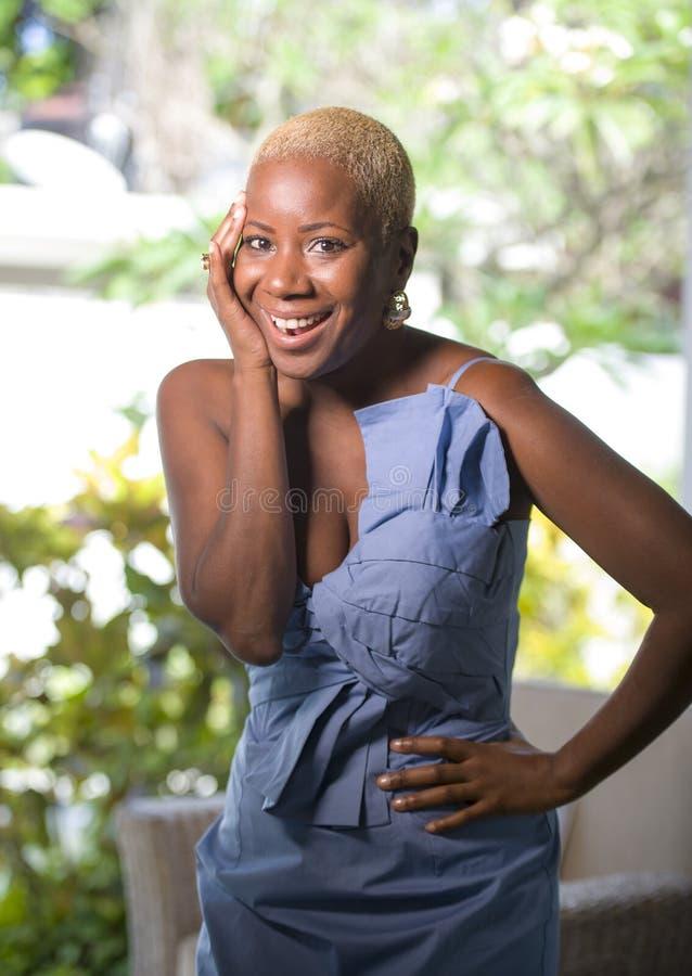 Levensstijlportret van jonge aantrekkelijke en blije zwarte afro Amerikaanse vrouw die gelukkig stellend vrolijk thuis terras met stock fotografie