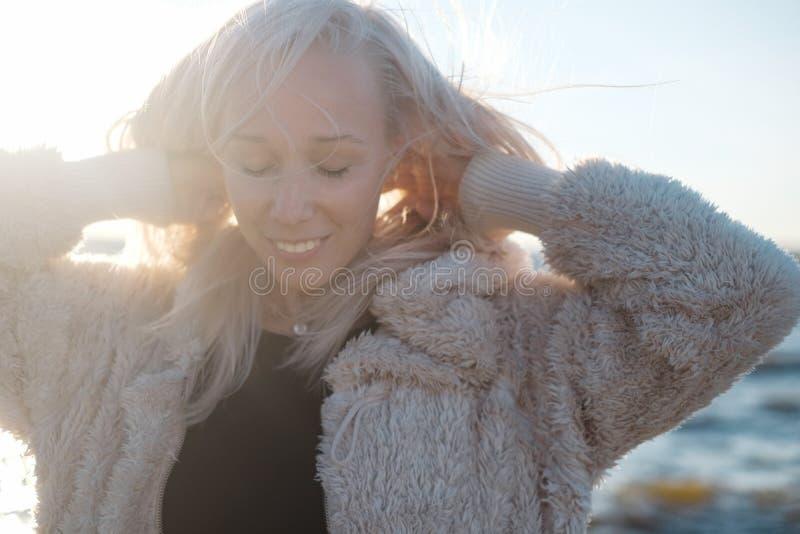 Levensstijlportret van jonge blondevrouw in winderige dag op zee royalty-vrije stock afbeeldingen