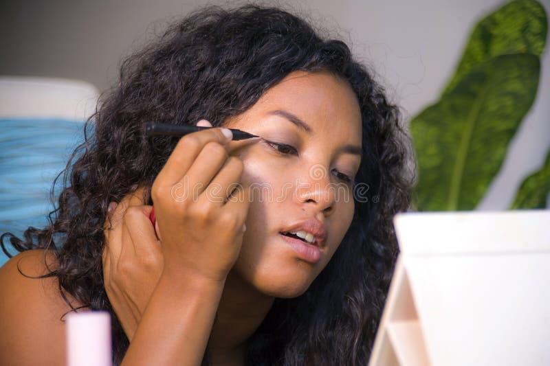 Levensstijlportret van jonge gelukkige en mooie Latijns-Amerikaanse vrouw die eyeliner gebruiken die oog met potloodvoering profi stock foto