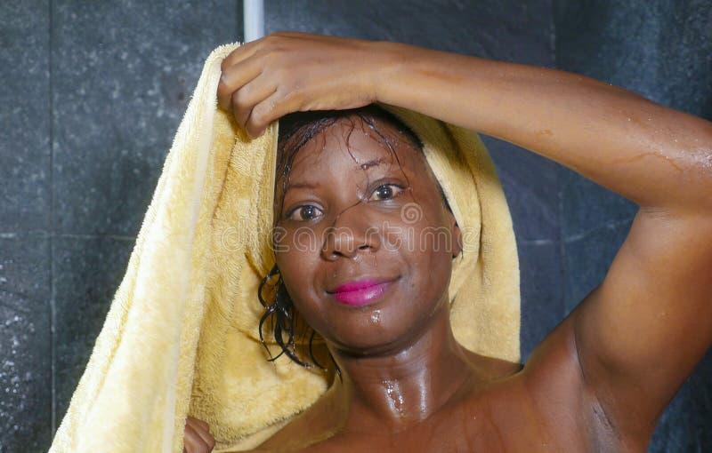 Levensstijlportret van jonge mooie en gelukkige zwarte Afrikaanse Amerikaanse vrouw gelukkig en vrolijk drogend haar glimlachen e stock afbeelding