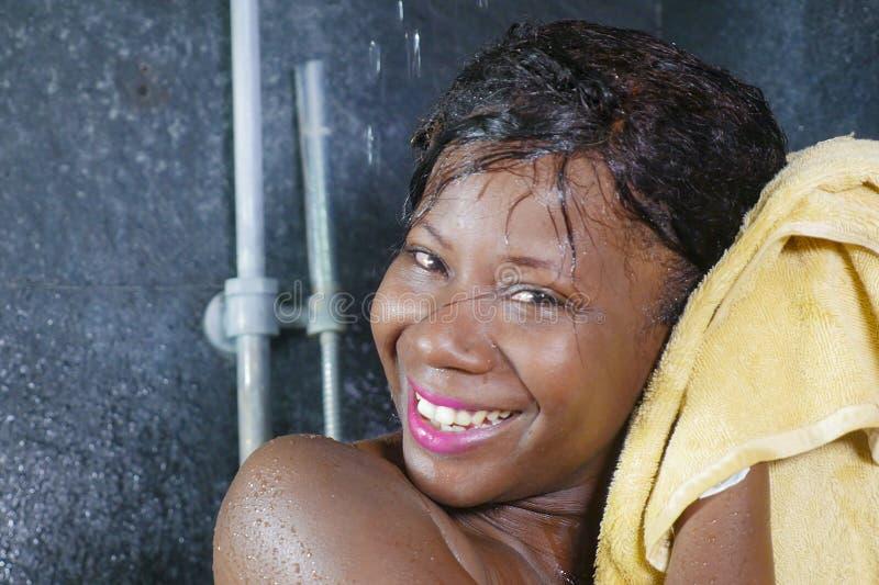 Levensstijlportret van jonge mooie en gelukkige zwarte Afrikaanse Amerikaanse vrouw gelukkig en vrolijk drogend haar glimlachen e stock afbeeldingen