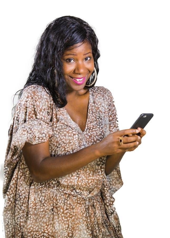 Levensstijlportret van jonge mooie en gelukkige zwarte afro Amerikaanse vrouw die in zoete kleding vrolijk gebruikend Internet ap royalty-vrije stock fotografie
