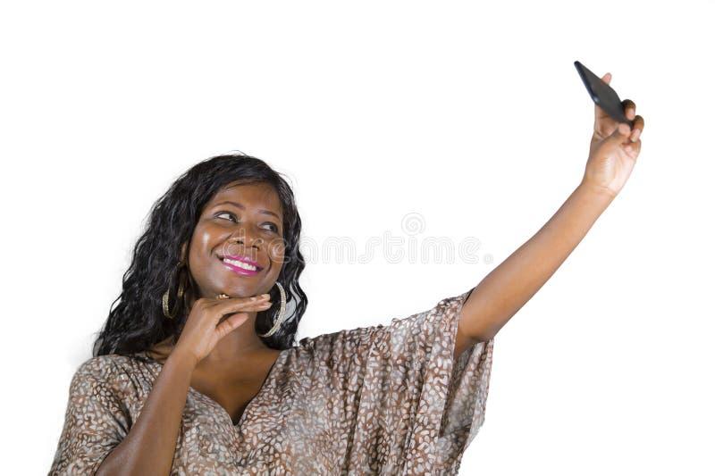 Levensstijlportret van jonge mooie en gelukkige zwarte afro Amerikaanse vrouw die in zoete kleding vrolijk gebruikend Internet ap royalty-vrije stock foto
