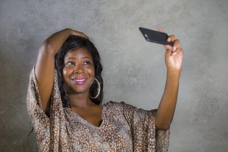 Levensstijlportret van jonge mooie en gelukkige zwarte afro Amerikaanse vrouw die in zoete kleding vrolijk gebruikend Internet ap royalty-vrije stock afbeeldingen