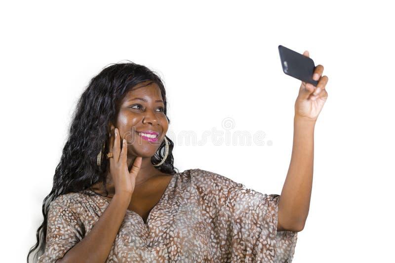 Levensstijlportret van jonge mooie en gelukkige zwarte afro Amerikaanse vrouw die in zoete kleding vrolijk gebruikend Internet ap royalty-vrije stock foto's