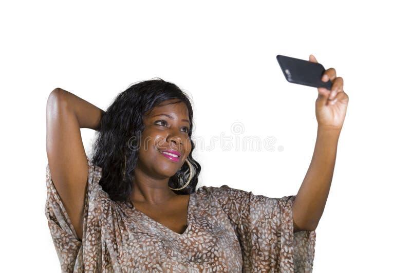 Levensstijlportret van jonge mooie en gelukkige zwarte afro Amerikaanse vrouw die in zoete kleding vrolijk gebruikend Internet ap royalty-vrije stock afbeelding