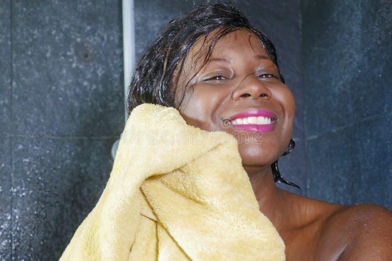 Levensstijlportret van jonge mooie en gelukkige zwarte afro Amerikaanse vrouw gelukkig en vrolijk drogend haar glimlachen en lich stock foto's