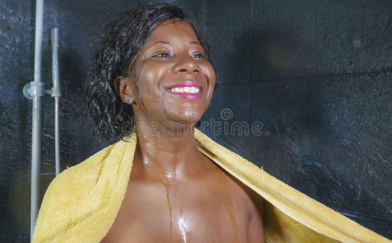 Levensstijlportret van jonge mooie en gelukkige zwarte afro Amerikaanse vrouw gelukkig en vrolijk drogend haar glimlachen en lich stock foto
