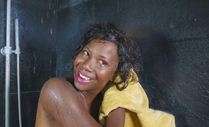 Levensstijlportret van jonge mooie en gelukkige zwarte afro Amerikaanse vrouw gelukkig en vrolijk drogend haar glimlachen en lich royalty-vrije stock foto