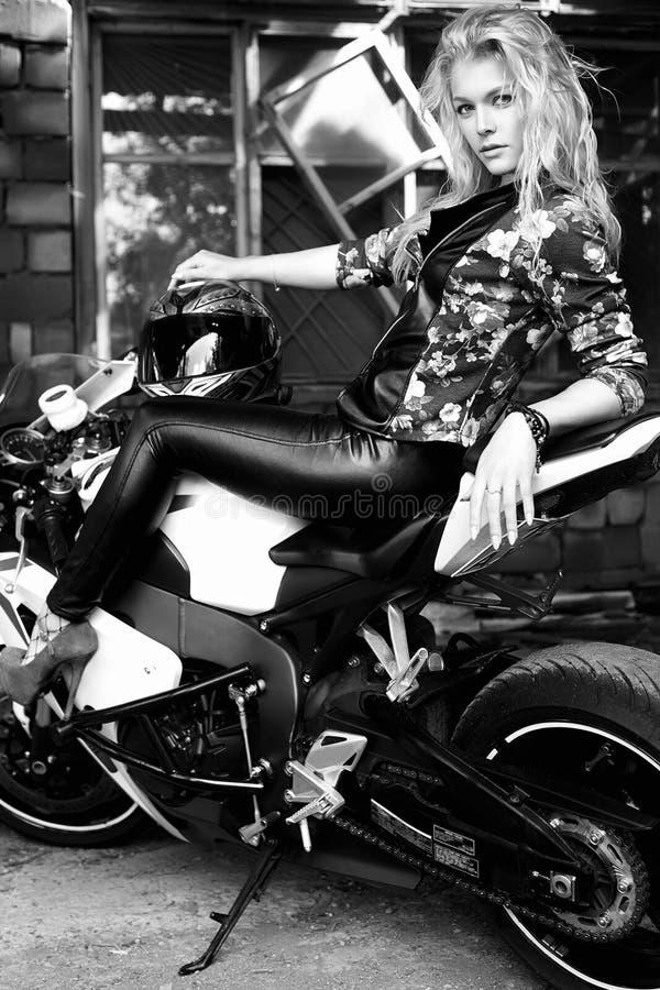 Levensstijlportret van sexy meisjeszitting op een motorfiets royalty-vrije stock foto's