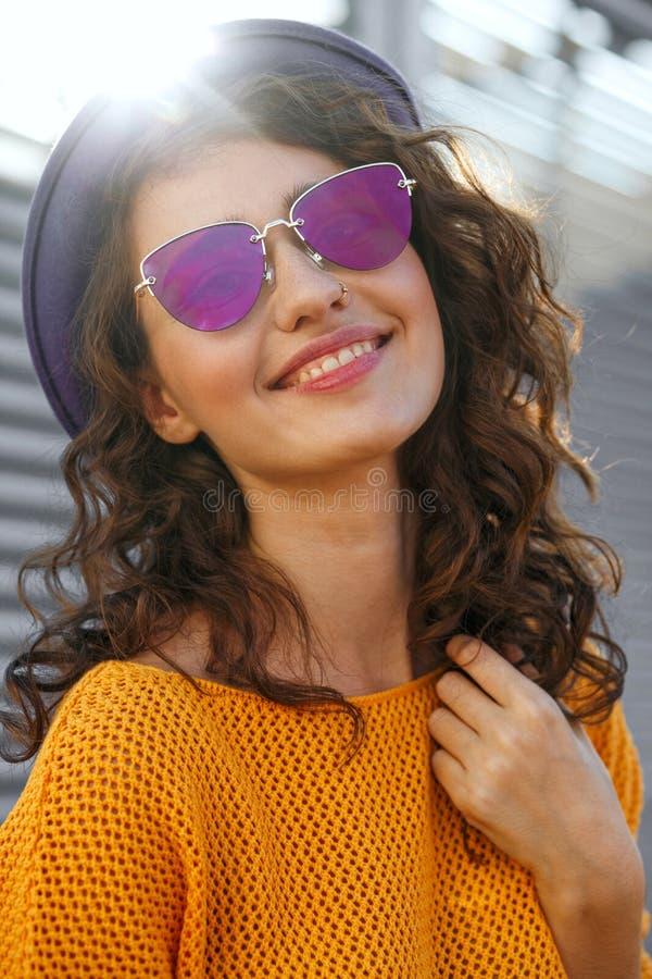 Levensstijlportret van vrolijke donkerbruine model dragende hoed en gl stock afbeeldingen