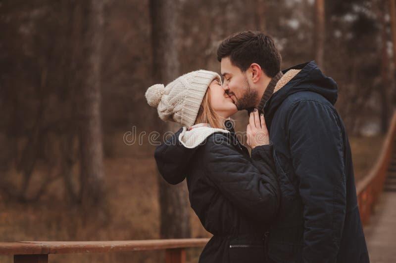Levensstijlvangst van het gelukkige paar kussen openlucht op comfortabele warme gang in bos stock fotografie