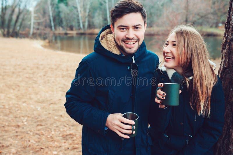 Levensstijlvangst van paar die hete thee openlucht op comfortabele warme gang in bos drinken royalty-vrije stock fotografie