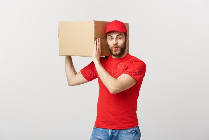 Lever Concept: Jonge Kaukasische knappe leveringsmens die een doos op schouder houden Geïsoleerdg over grijze achtergrond royalty-vrije stock foto