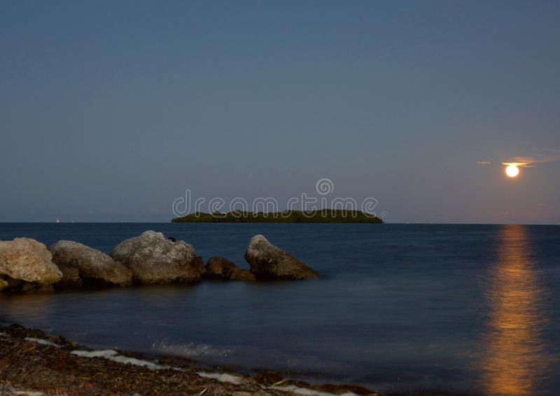 Lever de la lune au-dessus de l'océan avec une île photos libres de droits