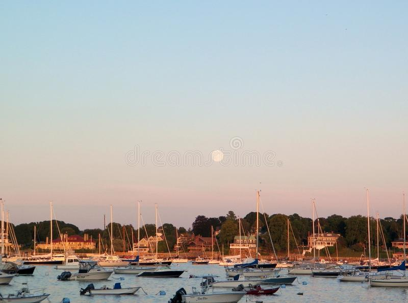 Lever de la lune au-dessus de port de la Nouvelle Angleterre avec des voiliers photographie stock libre de droits