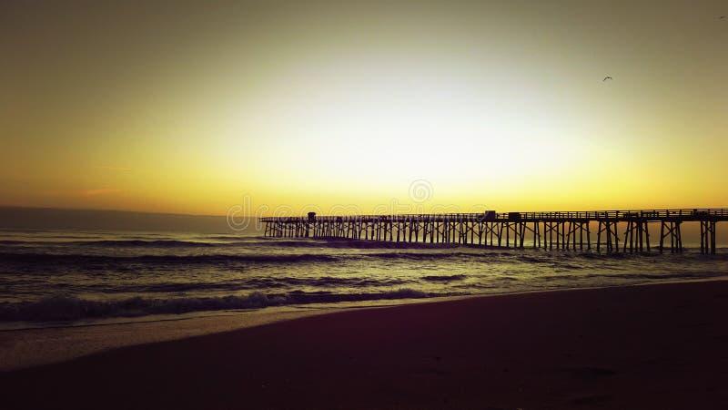 Lever de soleil à la plage avec le pilier et le ciel chaud photo stock