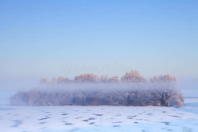 Lever de soleil au-dessus d'une île dans un lac congelé photos libres de droits