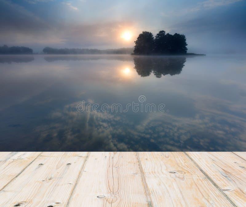 Lever de soleil au-dessus de lac paysage avec le plancher en bois de planches image libre de droits