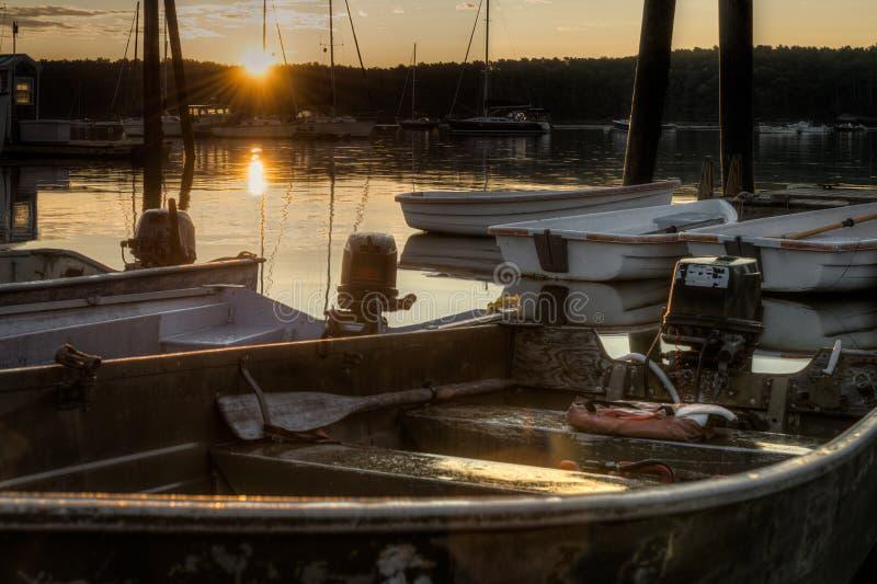 Lever de soleil au-dessus des bateaux à rames amarrés images libres de droits