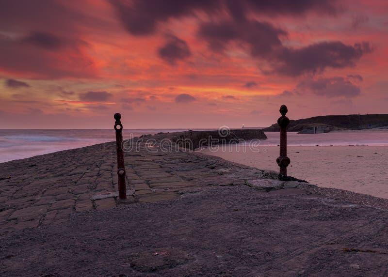 Lever de soleil au-dessus du pilier et de l'entrée du sud à la baie de Cullercoats sur la Côte Est du nord de l'Angleterre photographie stock