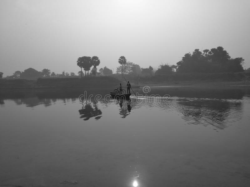 Lever de soleil au-dessus de la rivière et d'un bateau image stock