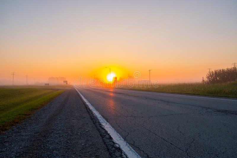 Lever de soleil au-dessus de route brumeuse vide photo stock