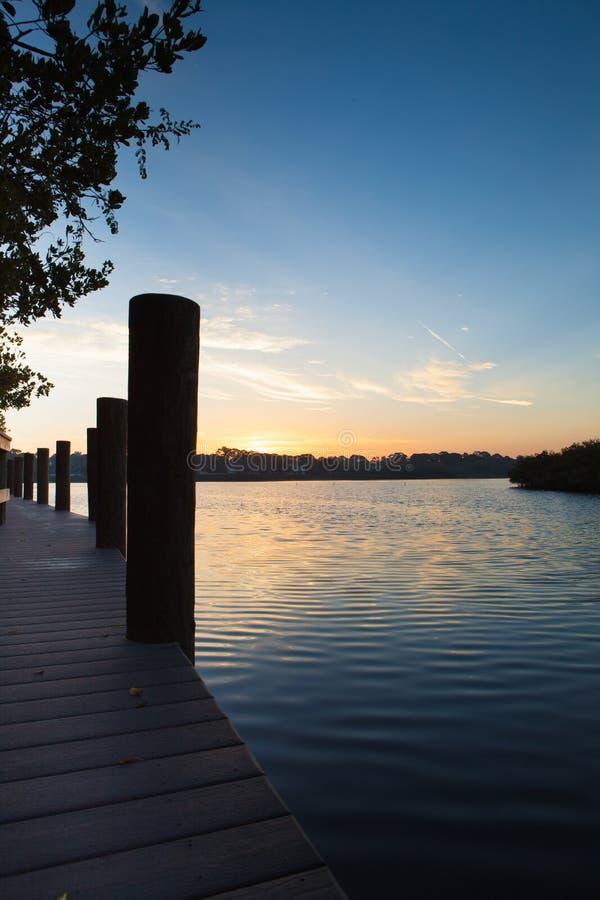 Lever de soleil au dock de bateau avec des empilages de bateau images stock