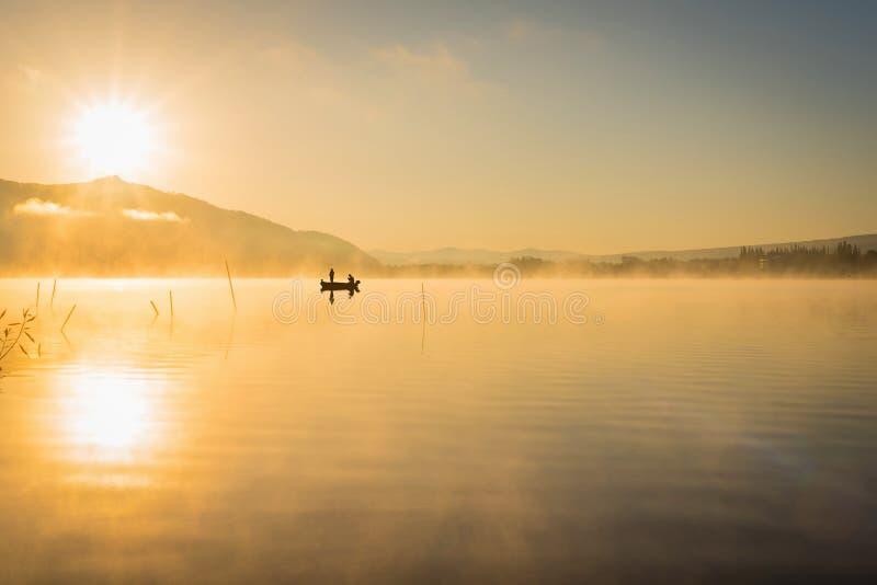 Lever de soleil au lac Kawaguchiko, les gens pêchant sur un bateau, silhoue image libre de droits