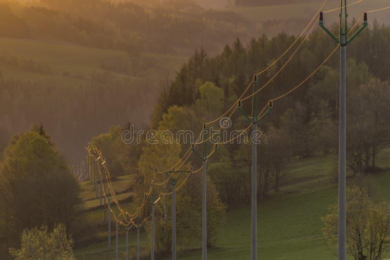 Lever de soleil avec les poteaux électriques près du village de Roprachtice photos libres de droits