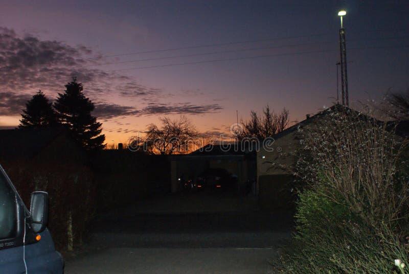 Lever de soleil avec les silhouettes foncées des maisons dans le voisinage résidentiel photographie stock libre de droits