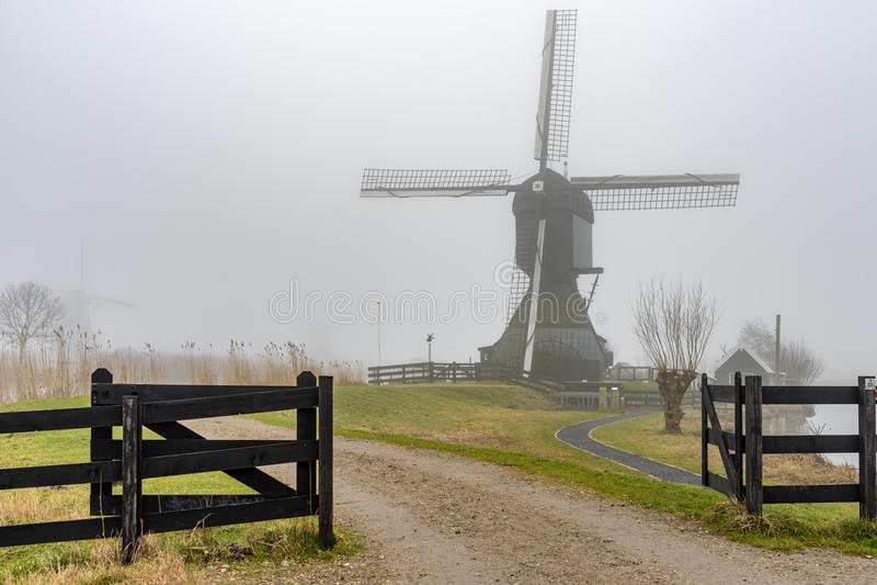 Lever de soleil brumeux et calme de moulin à vent photo stock